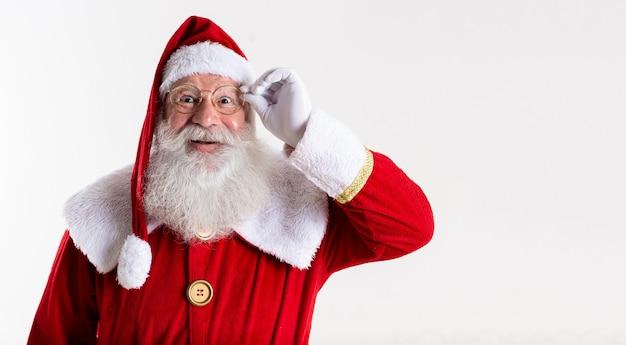 Santa claus in brillen kijkt naar de camera en glimlacht, op witte achtergrond