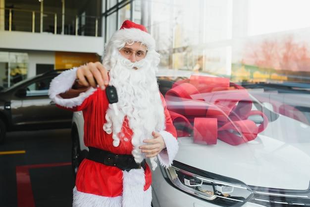 Santa claus in de buurt van een nieuwe auto in een autodealer.