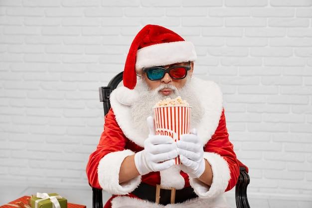Santa claus in fauteuil kijken naar gestreepte emmer popcorn