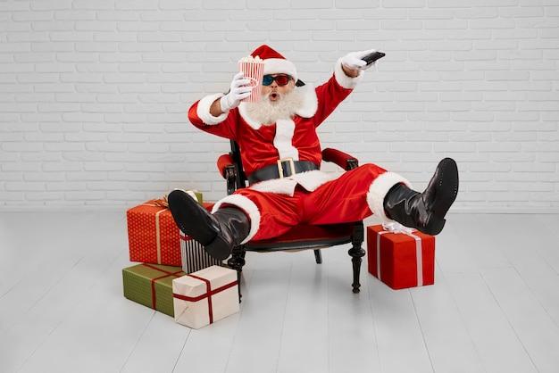 Santa claus in fauteuil tv kijken met popcorn in studio