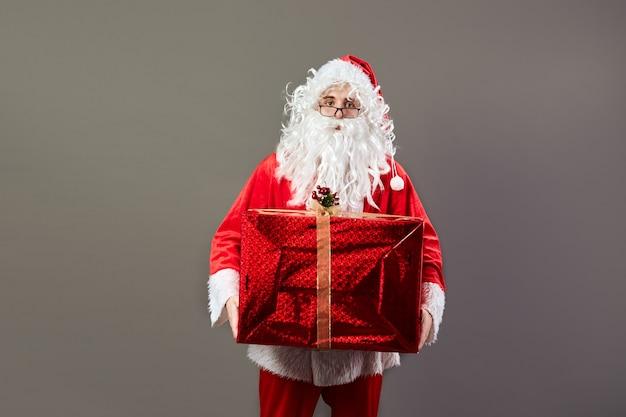 Santa claus in glazen houdt in zijn hand het enorme kerstcadeau op de grijze achtergrond. .