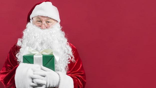 Santa claus in hoed die groene giftdoos houdt