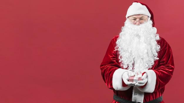 Santa claus in hoed die kleine geschenkdoos