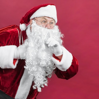 Santa claus in rode hoed die geheim gebaar toont