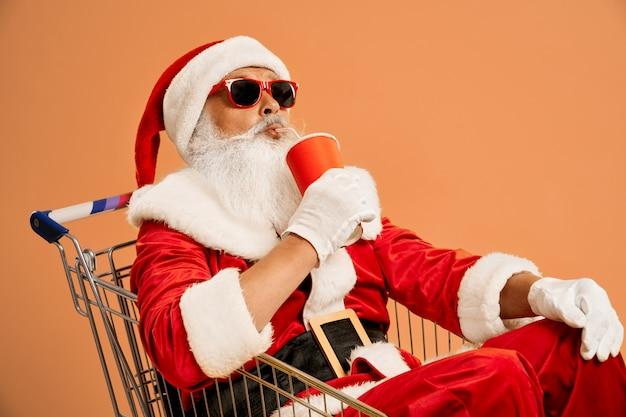 Santa claus in winkelwagen drinken uit rode papieren beker