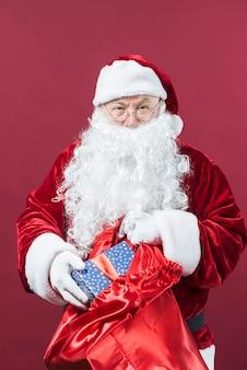 Santa claus krijgt geschenkdoos van grote zak