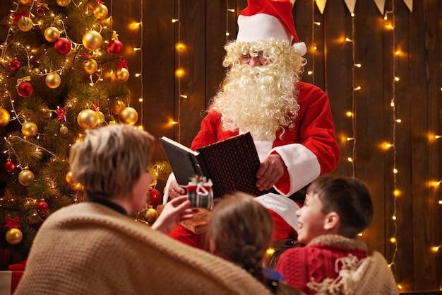 Santa claus leesboek voor familie zitten in de buurt van versierde kerstboom