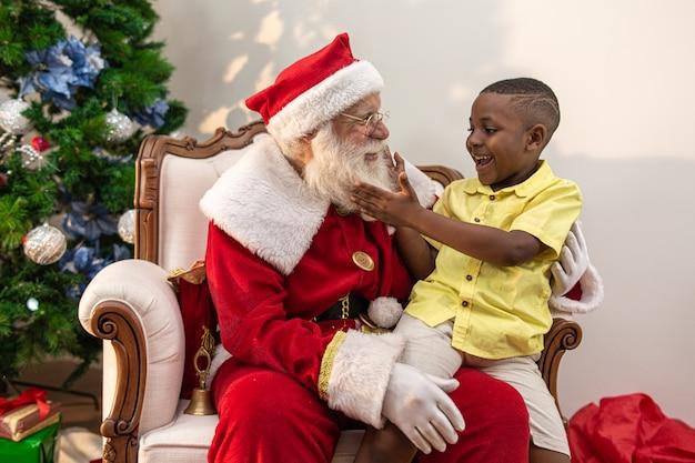 Santa claus levert een geschenkdoos aan een kleine afrikaanse jongen