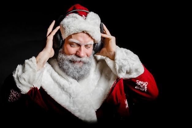 Santa claus luistert naar muziek met een koptelefoon op een zwarte achtergrond