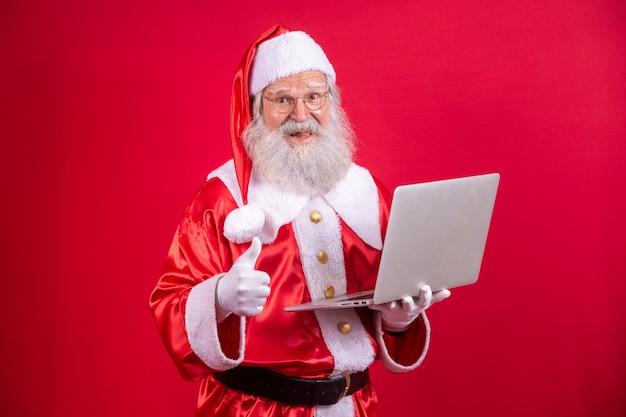 Santa claus met behulp van een laptop met zijn duim omhoog