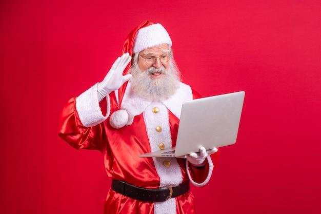Santa claus met behulp van een laptop op rode achtergrond.
