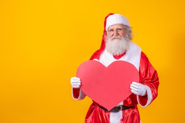 Santa claus met grote rode hartkaart op gele achtergrond. romantische kerstman.