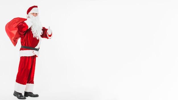 Santa claus met zak die duim op gebaar toont