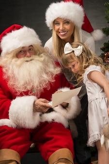 Santa claus om thuis te zitten met schattig klein meisje en haar moeder en het lezen van brief