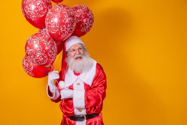 Santa claus op gele achtergrond met rode ballonnen.