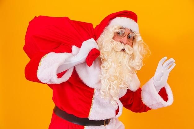 Santa claus op gele achtergrond met zak met geschenken achter zijn rug. sinterklaas doet een verrassing op kerstnacht