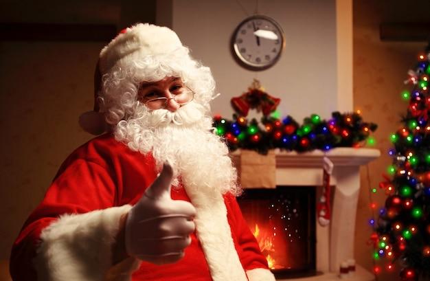 Santa claus opstaan met duimen omhoog. huisdecoratie Premium Foto