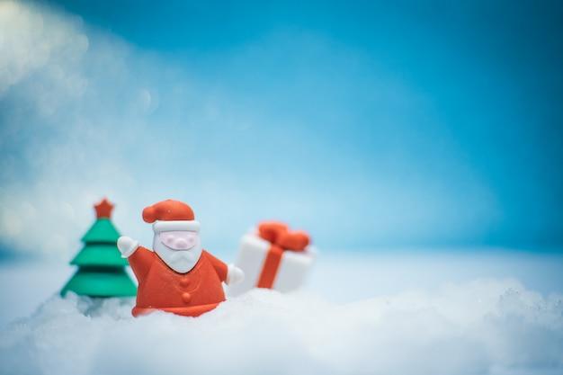 Santa claus-poppen en kerstboom en giftvakje op sneeuw