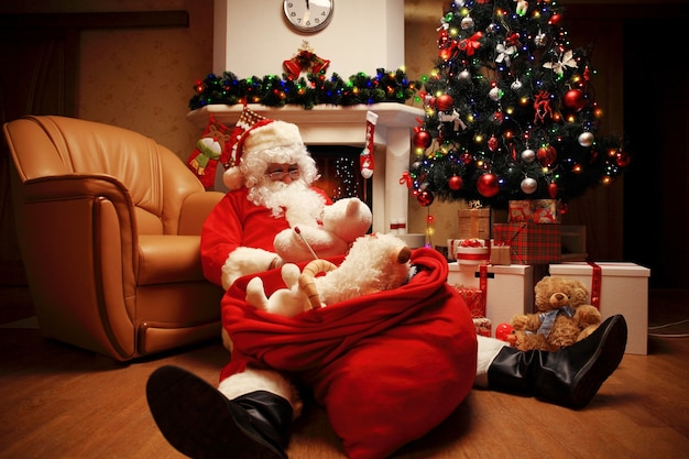 Santa claus rust in een comfortabele stoel bij de open haard thuis