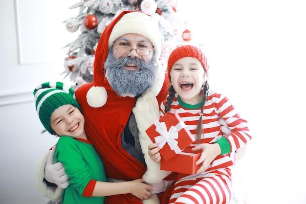 Santa claus's helpers.schattige kinderen in kerst elf kostuums in een kamer prachtig ingericht voor kerstmis. tijd van wonderen. cadeautjes van sinterklaas.