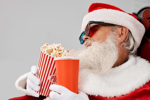 Santa claus-slaap in leunstoel met popcorn en cola