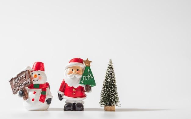 Santa claus, sneeuwman en kerstboom voor kerstmisachtergrond