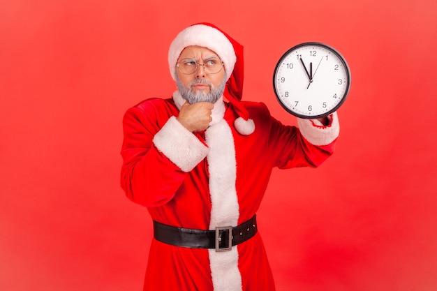 Santa claus staande met wandklok, kin vasthoudend, wachtend op kerstfeest, wegkijkend.