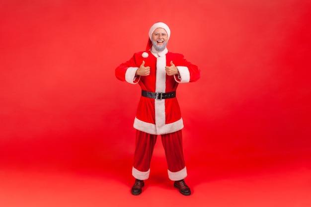 Santa claus staat en toont duim omhoog, goedkeuring handteken, tevreden met resultaat.