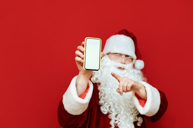 Santa claus staat met smartphone in de hand op rood en toont vinger op leeg wit scherm