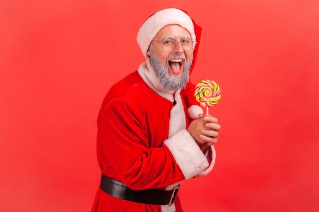 Santa claus staat met zoete lolly in handen, kijkend naar de camera.