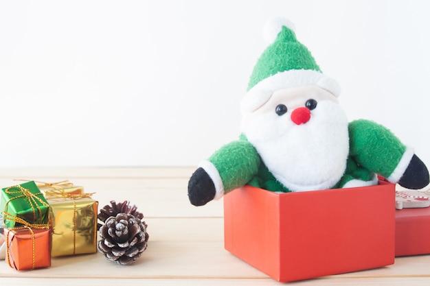 Santa claus-stuk speelgoed zitting in rode doos, kerstmisgift, vakantieconcept