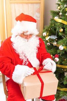 Santa claus-verpakkende gift met lint