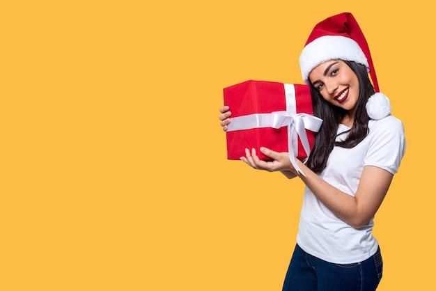 Santa claus-vrouw die een geïsoleerde gift houdt