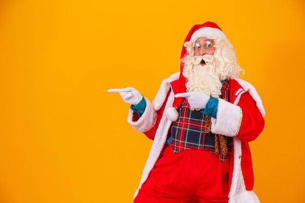 Santa claus wijst naar de vrije kant voor tekst aan de linkerkant