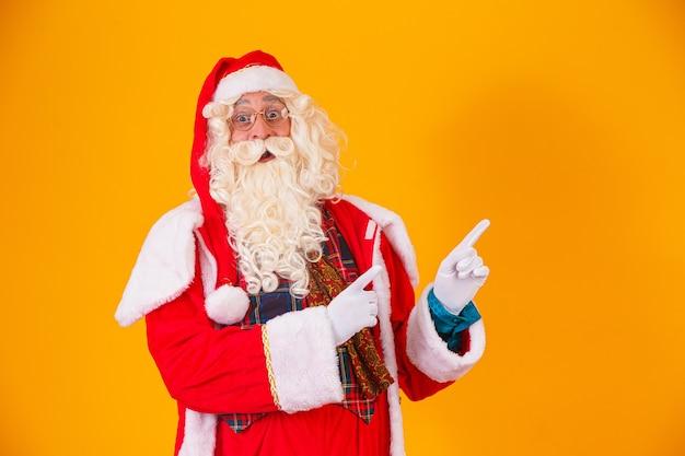 Santa claus wijst naar de zijkant met ruimte voor tekst