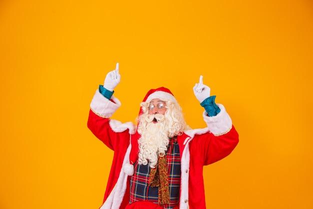 Santa claus wijst omhoog in de ruimte voor tekst