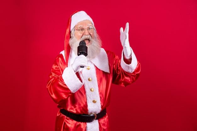 Santa claus zingt of spreekt in een studiomicrofoon. vrolijk kerstfeest. omroep. omroeper. promotie. kerst muziek concept