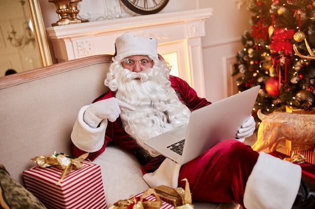 Santa claus zit bij hem thuis en leest e-mail op laptop met ñ hristmas verzoekende of wenslijst bij de open haard en boom met geschenken. nieuwjaar en prettige kerstdagen, prettige feestdagen concept