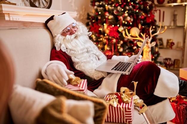 Santa claus zit bij hem thuis en lezen van e-mail op laptop met kerstverzoek of verlanglijstje bij de open haard en de boom met geschenken. vrolijk kerstfeest, prettige feestdagen concept