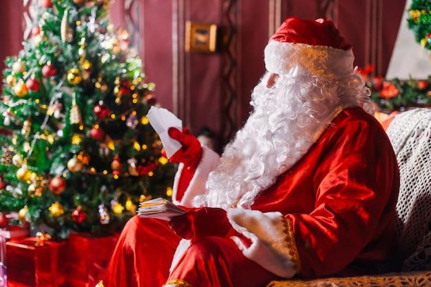 Santa claus zit naast een kerstboom