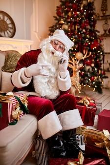 Santa claus zittend op de bank en praten over de mobiele telefoon in de buurt van de open haard en de kerstboom met geschenken.