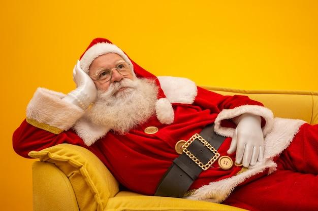 Santa claus-zitting op een gele laag op geel