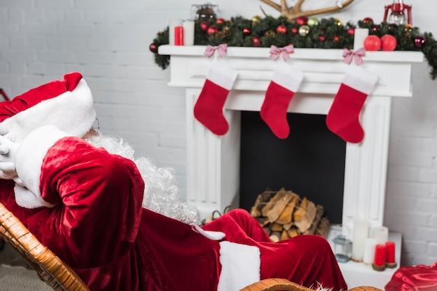 Santa claus-zitting op schommelstoel met handen achter hoofd
