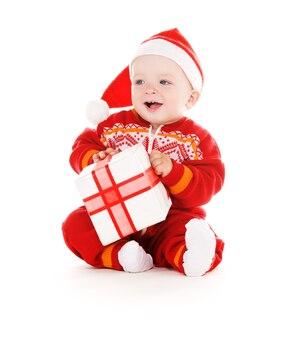 Santa helper baby met kerstcadeau over witte muur