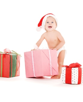 Santa helper baby met kerstcadeaus over witte muur