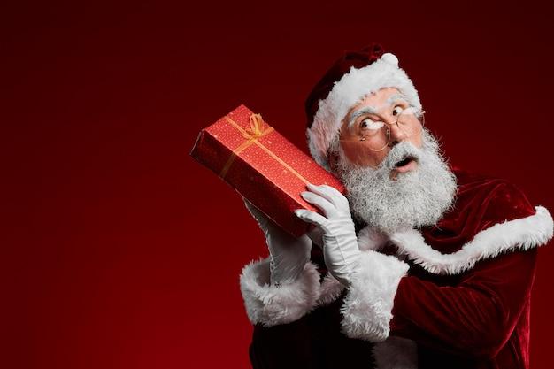 Santa holding christmas present o red
