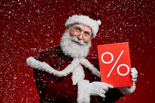 Santa holding sale sign in sneeuw