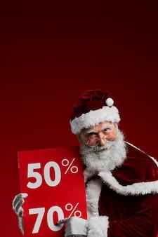 Santa holding sale sign op rood