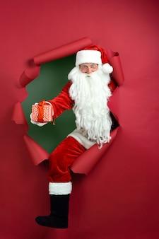 Santa man houdt geschenkdoos in de hand door een gat in papier.