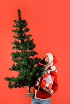 Santa man houdt kerstcadeau en dennenboom in de hand bebaarde man in kerstkostuum met geschenkdoos en